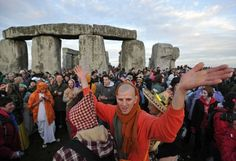 Revellers celebrate as the sun rises behind Stonehenge during the pagan festival Summer Solstice in Wiltshire