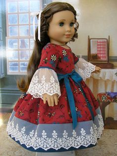 Here is an American Girl doll mid-1800s gown, featuring authentic reproduction fabric and embroidered netting lace. The cotton fabric, in olde red and a blue-ish teal, has the year 1850 printed on the fabric selvedge (edge), printed in a graceful, trailing floral design. A matching blue-ish teal cotton fabric is used for accents. The lace on the hemline and sleeves is cotton, including the netting, so it is soft and not stiff at all. A matching rayon ribbon is tied in a separate sash. The…