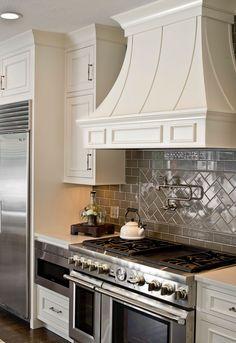 White Cabinets, gray subway tile, pot filler, Thermadore Range. White hood. Herringbone backsplash
