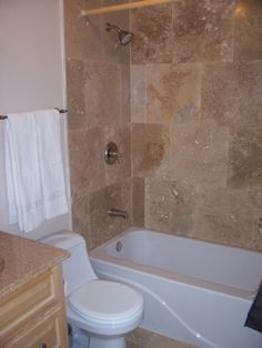Travertine stone tile floors & tub surround, tub/shower combo, and maple vanity with granite counter top.