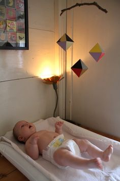 """Alice Octahedrons: This mobile hangs over the changing table. I used different coloured card and also shiny black and gold mirror foil. For contrast I used a branch from our garden to suspend them from."" (et d'autres exemples d'aménagements de chambre plus ""puristes"")"