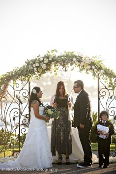 wrought iron arbor with floral cascade of seeded eucalyptus and vandela roses #embellishmint
