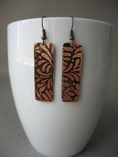 These lovely hand etched copper earrings are 1.5 inches long. They have copper ear wires and are sealed to preserve their color contrast.