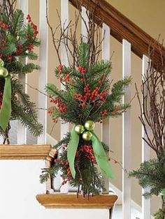 Instead of wrapping garland around my staircase, this is a different idea! Sprigs of garland and twigs. Love it!