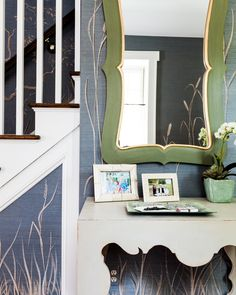 Contemporary foyer features a wall clad in blue pattern grasscloth lined with a light gray carved console table under a green mirror accented with gold trim.