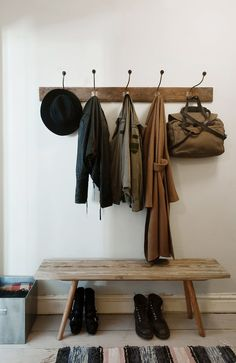 Entry way with hooks for hanging coats and hats, a bench for putting on shoes or taking off, and storage