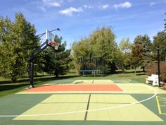 The Pro Dunk Gold Basketball System sits center on this court. White striping on the concrete slab provides key and three-point line.