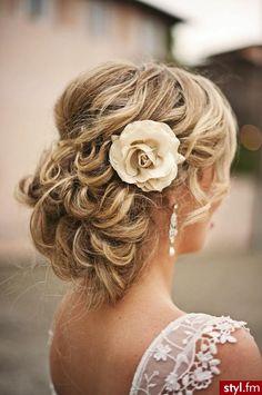 Długie, blond, kręcone włosy upięte w niski kok z tyłu głowy, we włosy wpięty duży kwiat. Fryzura ślubna, wieczorowa, na studniówkę.
