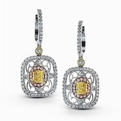 Featuring delicate vintage-inspired styling, these three-tone dangle earrings are set with .70 ctw round cut white diamonds and .50 ctw yellow oval diamonds.