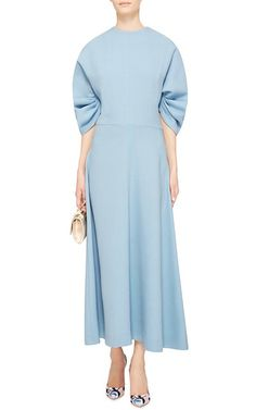 Filtering her thoroughly ladylike aesthetic through a reverie-inducing, Wes Anderson-esque filter, for Fall '15 the red carpet favorite delivers this **Emilia Wickstead** Dana dress in powder blue wool. Crafted in Italy, this dress exudes elegance in a softly draped, ladylike silhouette with sculptural wide sleeves.