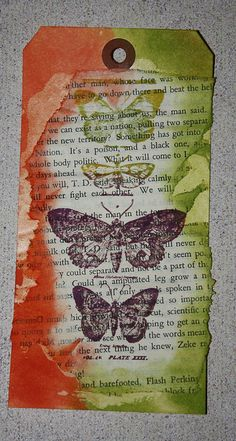 Tim Holtz Stamps and Distress Inks over a book page background.