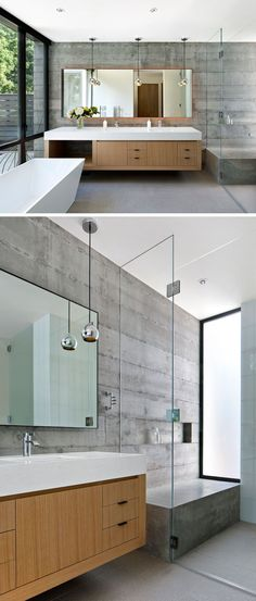 In this modern bathroom, the concrete walls and details, like the white standalone tub, floating double vanity with ample storage, and large backlit mirror, give the bathroom a contemporary feel while at the same time give it a warm and inviting look. In the shower, there's a large concrete bench to match the concrete walls, and a glass shower screen keeps the vanity dry.