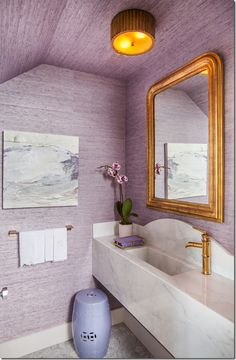 new powder room with a marble sink and gilt mirror.  The walls are lilac grasscloth.