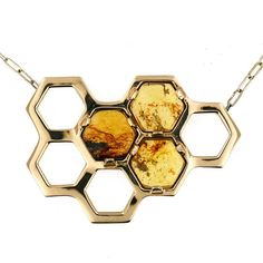 Inspired by my fascination with bees and my love for amber, HONEY is a bronze honeycomb pendant with three prong set Chiapas amber hexagons. The richly colored