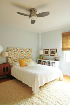 Like the ceiling fan  The instant serenity of the bedroom is achieved by the soft white bedspread, calming light blue wall color, whimsical headboard, wooden accents like the mid-century credenza and rocking chair and the natural textures such as the bamboo window chair.