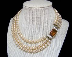 Mid Century creamy faux pearl bead multi strand choker length necklace Rectangular amber rhinestone surrounded by crystal rhinestones clasp Perfect vintage bridal jewelry Silver tone setting 14, 15.5, and 17 inch long strands 6mm glass pearls Very good condition I specialize in vintage beaded jewelry, please visit my shop to see more International buyers welcome, overcharges are refunded Flat rate priority shipping is optional 80217  Credit cards and Paypal accepted