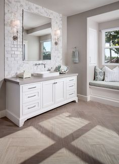 The master bathroom features a wood-grain tile in herringbone pattern and a Calacatta Gold marble subway tile backsplash.