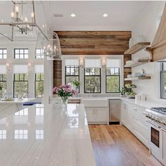light stone counters, white shaker cabinets, rustic wood feature-wall, rustic wood shelves and trim details, rectangular hardware, glass pendants, white walls