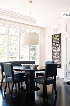 chic dining room design with Jonathan Adler Robert Abbey brass drum meurice pendant, round espresso dining table, leather dining chairs, subway sign art, glossy, windows, crown molding and glossy black wood floors.