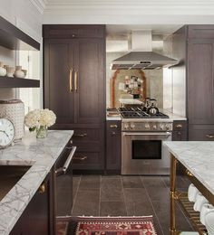 Beautiful kitchen features dark brown stained cabinets adorned with brass cup pulls topped with grey and white marble countertops fitted with a stainless steel sink and gooseneck faucet placed under dark brown stacked floating shelves illuminates by antique brass sconces. Elizabeth Krueger Design