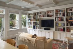 traditional family room by Gast Architects - center speaker below tv, note side speakers among books