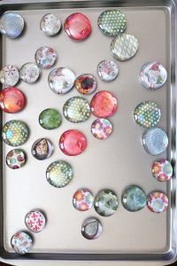 "Tutorial For craft fair magnets Glass Magnet Tutorial Materials: 1 inch glass pebbles (Dollar Tree- about come 30 in a bag) Crystal Effects 1"" circle punch /Patterned paper of your choice Hot glue gun High energy magnet buttons"