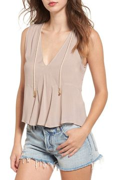 among the roses drape tank by Somedays Lovin. Playful rope ties dangle from the neckline of this lightweight jacquard tank styled with a subtle peplum hem.