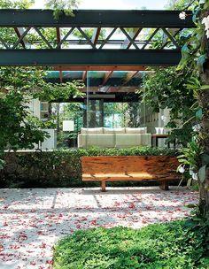 O banco do designer Hugo França fica numa das sombras mais gostosas do jardim, sob um flamboyant de 15 anos, próximo à casa. A área é contornada por uma cerca viva de gardênia (1). Atrás dela, dois exemplares de magnólia (2). O piso de mármore travertino  (Foto: Casa e Jardim)