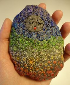 Stitched pebble with chakra colors.