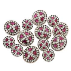 A SET OF RUBY AND DIAMOND SHERWANI BUTTONS. Comprising seven large and six small buttons, each circular panel with old-cut millegrain-set diamond cross motif to a fancy-cut ruby surround, within a similarly-set diamond border, 2.2cm and 1.5cm respectively