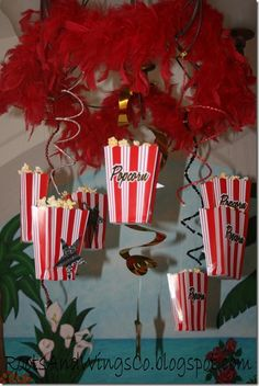 Such a perfect hanging centerpiece: red feather boa and popcorn containers (with real popcorn) hang from the chandelier.