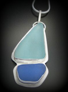 """Our custom designed, genuine sea glass necklace in this nautical sailboat design features two smooth, Pacific sea glass pieces. The aqua """"sail"""" piece measures just under 1""""tall and likely originates from canning jar or electric insulator glass. The deep, dusty blue""""boat"""" piece is highly rareand measures right at 5/8"""" wide. The pieces are snugly artisan set all around in sterling silver on a solid sterling silver backplate. They are soldered to a sterling silver slide bail that's…"""