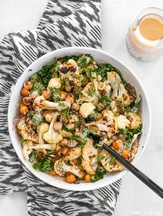 This Roasted Cauliflower Salad combines sweet roasted red onions, spiced chickpeas, tender cauliflower, and a tangy lemon tahini dressing. BudgetBytes.com #ad