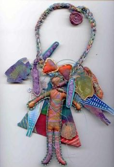 This necklace has stuffed shapes, laminated shapes, air-dry clay shapes, and lots of little cord pieces hanging throughout the design.  The center piece started as a doll and then I created a fabric triangle to put behind the doll.  The necklace cord is crocheted.Sherrill Kahn