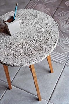 Faux Moorish design: small table or flower stand with a large crochet doily stretched over it.