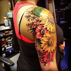 Colorful collection of flower arm tattoos. The sunflowers are the central part of the design and they contrast well with the colors of the pother flowers behind it.