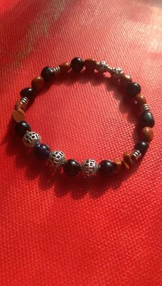 Women's beaded bracelet. Blue Tiger Eye, Sapphire blue goldstone and Red Jasper semi precious stones. Filigree Tibetan silver spacer beads.