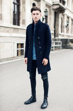 Perfect the smart casual look in a navy overcoat and deep blue ripped slim jeans. To break out of the mold a little, rock a pair of black leather chukka boots.  Shop this look for $191:  http://lookastic.com/men/looks/blue-denim-shirt-navy-overcoat-navy-skinny-jeans-black-desert-boots/4962  — Blue Denim Shirt  — Navy Overcoat  — Navy Ripped Skinny Jeans  — Black Leather Desert Boots