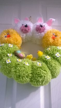 Handmade wreath from pompoms, decorated with Easter chicks, felt flowers and other embellishments,