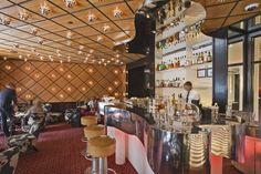 Spivak Architects - The Mark Restaurant by Jean-Georges. Chrome mirror-finish custom organic shape bar, Chrome flush-mounted lights on veneer ceiling & walls.