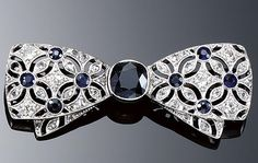SAPPHIRE AND DIAMOND BROOCH, 1920S.  Designed as a tied bow, centring on a cushion-shaped sapphire to ribbons pierced with a flower head design highlighted with single- and rose-cut diamonds and circular-cut sapphires.