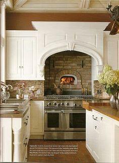 brick back splash and lovely white cabinets