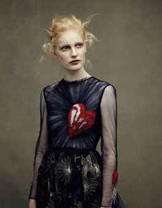 Valentino Fall 2014 rtw show ended with Ine Neefs wearing a navy tulle dress embroidered with a naively rendered heart over one breast and stars … Read More