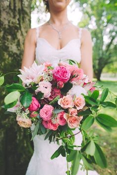 Full & wild bouquet in shades of pink with ranunculus, garden roses, king protea, and peonies -