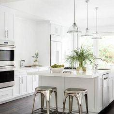 White KItchen with Dark Wood Floors and Industrial Counter Stools