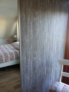 moderne shuifdeur van een inbouwkast, een behang van houtstructuur er op plakken en het heeft een leuk landelijk effect.