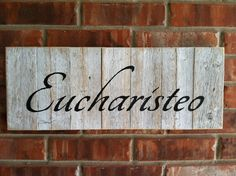 EUCHARISTEO sign in black paint on white dry brushed and sanded fence wood