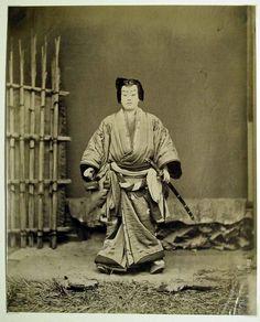 Actor in samurai dress near gate, ca. 1870s