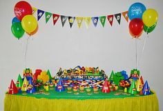 Lego birthday party decorations - red, blue, green and yellow balloon bouquets, Lego playset centerpiece and colorful banner. Lovely party set up..