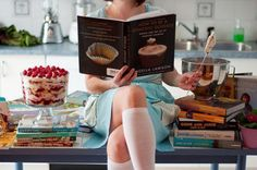 Woman sitting on the kitchen table and reading cooking recepies
